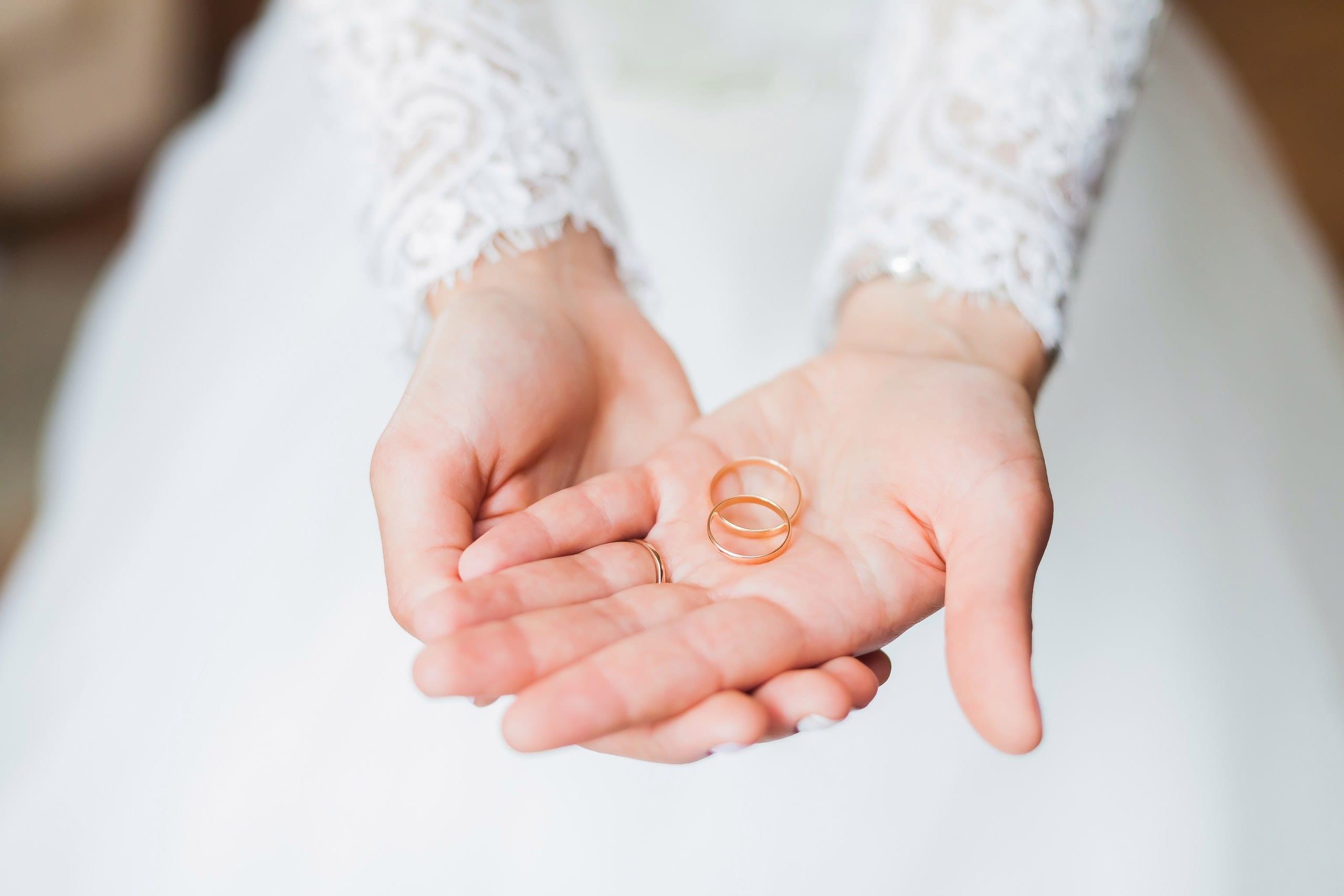 bruid met trouwringen in haar hand
