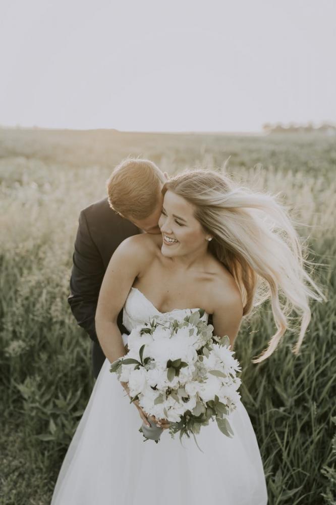bruidspaar lachend houden elkaar vast in graanveld