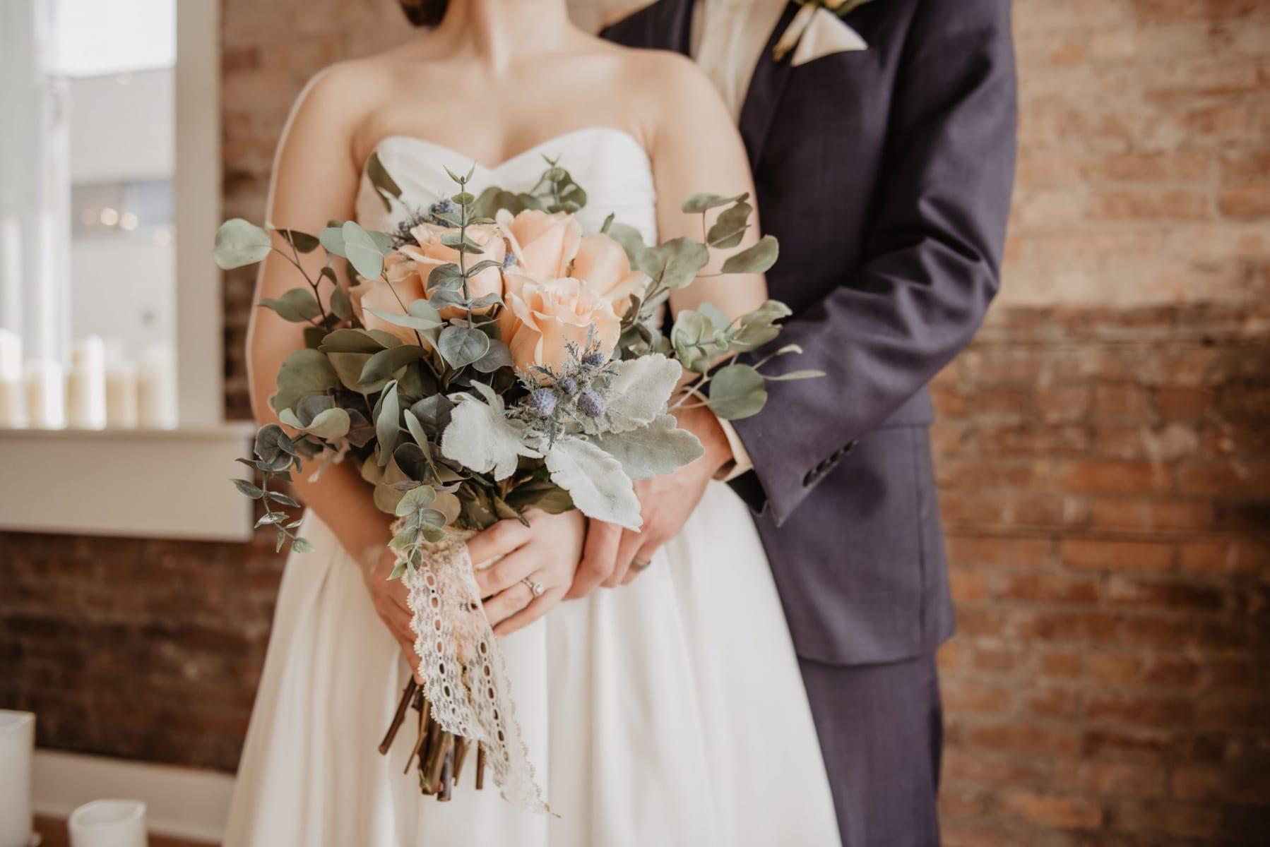 bruidspaar houden elkaar vast met boeket in handen